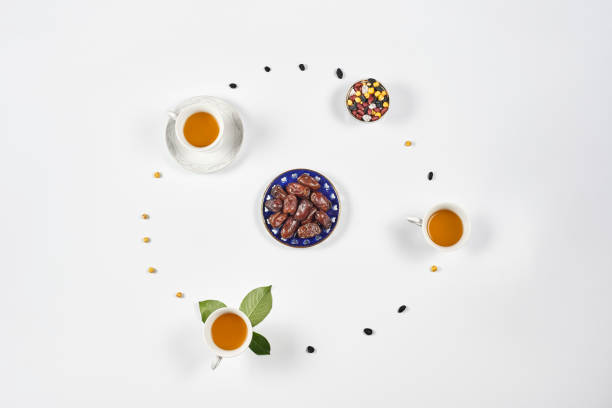Minimalistic Ramadan Background Minimalistic Ramadan Background. Cups of sweet green tea, date fruits and raisins placed in circle. muziekfestival stock pictures, royalty-free photos & images