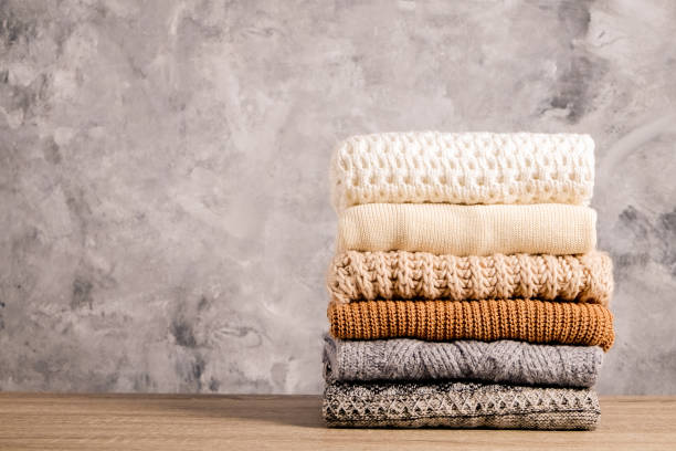 Minimalistic rustic composition with stacked vintage knitted easy chic oversized style sweaters, knitwear outfit. Bunch of knitted warm pastel color sweaters with different knitting patterns folded in stack on brown wooden table, grunged concrete wall background. Fall winter season knitwear. Close up, copy space sweater stock pictures, royalty-free photos & images