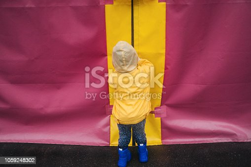 Minimalistic shot of little  boy in yellow raincoat on pink background