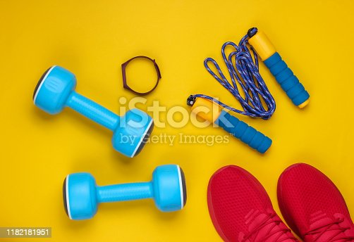 istock Minimalistic sport still life. Sports outfit. Red sports shoes for training and blue plastic dumbbells, jump rope, smart bracelet on a yellow background. Top view 1182181951