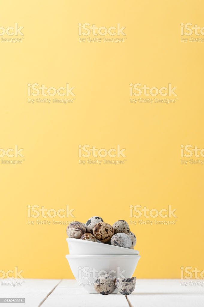 Minimalistic still life: fresh sawed eggs in a miniature white bowl on a yellow pastel background. stock photo