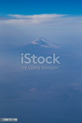 An aerial view looking down on Mount Fuji in the clouds. Some snow can be seen on the mountain. There is plenty of copy space for text around the mountain.