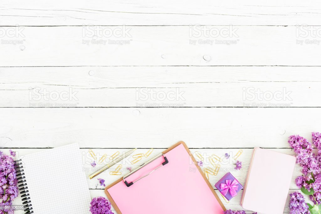 Minimalistic workspace with clipboard, notebook, pen, lilac, box and accessories on wooden background. Flat lay, top view. Beauty blog concept. royalty-free stock photo