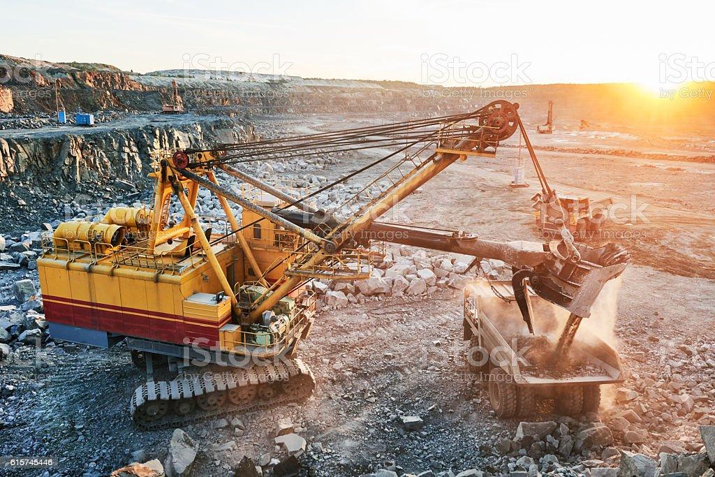Mining. excavator loading granite or ore into dump truck stock photo