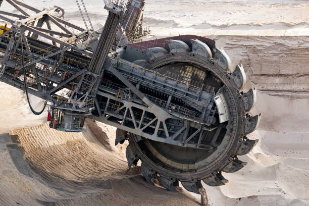 Mining machinery open pit mine Huge bucket-wheel excavator mining lignite (brown-coal) in an open pit mine. tagebau stock pictures, royalty-free photos & images