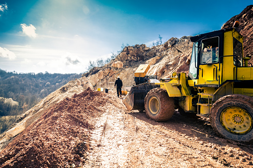 Wide angle color image depicting a mine working busy working outdoors at a limestone quarry. Rear view image of the worker while a yellow industrial digger is in the foreground. Bright blue sunny sky with cloudscape. Plenty of room for copy space.