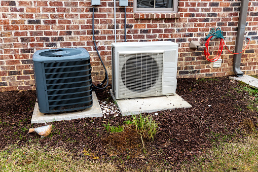 istock Mini-split air conditioner unit and full Compressor next to home, with copy space 1204424759