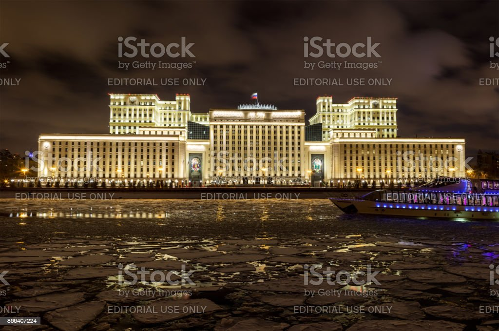 Ministry of Defense of Russia in the late evening in winter on a background of cloudy sky. On the front panel Moscow River covered with ice floes and pleasure boat. Colorful nighttime illumination stock photo