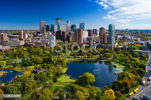 Minneapolis aerial with Downtown Minneapolis skyline in the background and Loring Park with Loring Pond in the foreground, during early autumn.