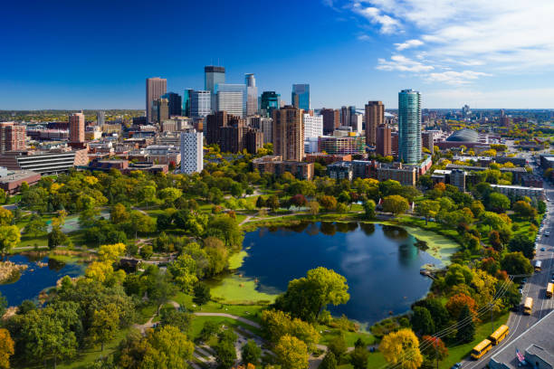 Minneapolis Skyline Aerial With Park And Lake Minneapolis aerial with Downtown Minneapolis skyline in the background and Loring Park with Loring Pond in the foreground, during early autumn. minnesota stock pictures, royalty-free photos & images