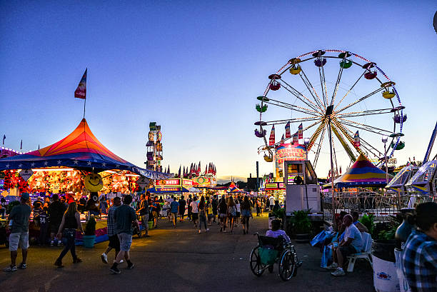 minnesota state fair's busy midway area at dusk - carnival stock photos and pictures
