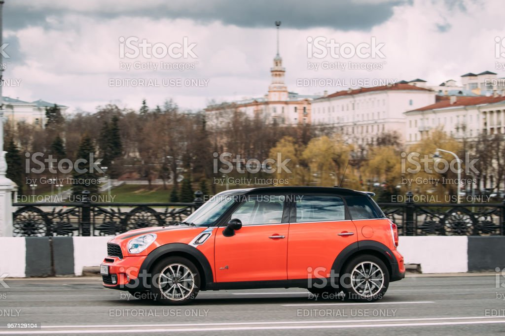 Minsk, Belarus. Orange Color Mini Cooper All 4 Car With Woman Driver In Fast Motion On Street stock photo