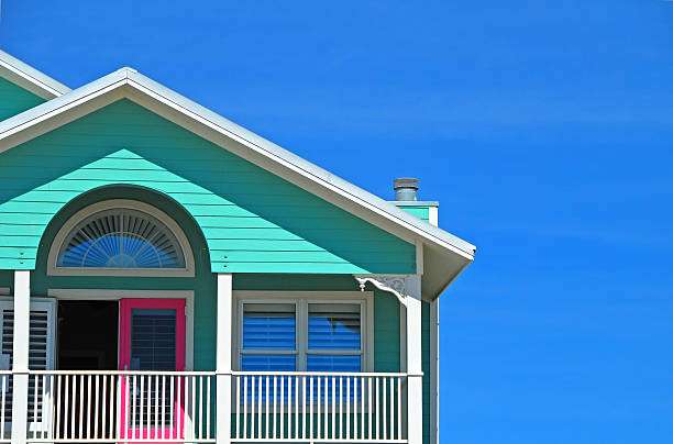 Mint and Pink Coastal HOme Bright beachfront home with mint siding and pink doors holiday villa stock pictures, royalty-free photos & images