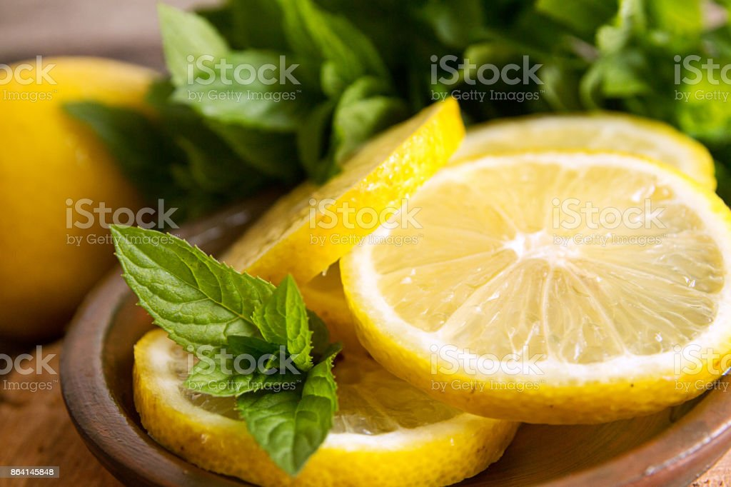 Mint and slices of lemon on old wooden background. royalty-free stock photo