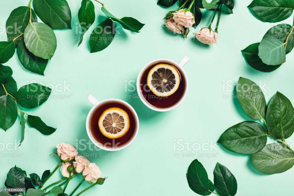 Food-drink mint concept. Two cups of hot tea with lemon surrounded by...
