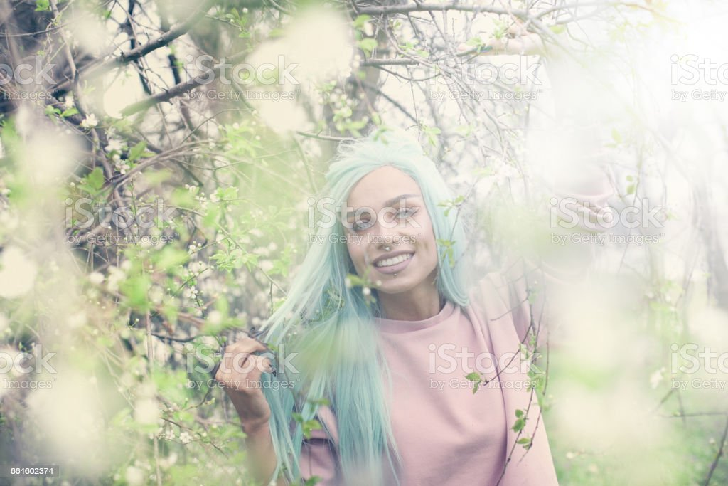 Mint haired young woman in cherry blossom. stock photo