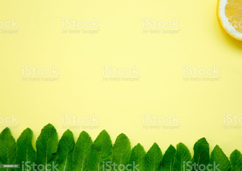 Mint leaves and slice of lemon on yellow background. Colorful summer pattern. stock photo