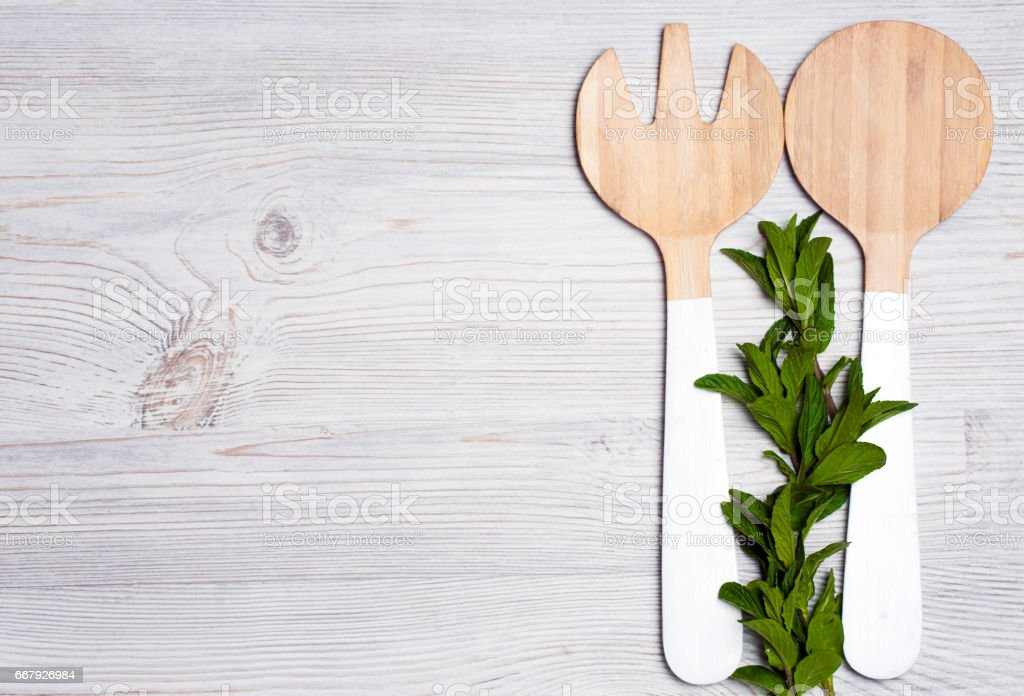 mint leaves with wooden cutlery on white wooden background stock photo