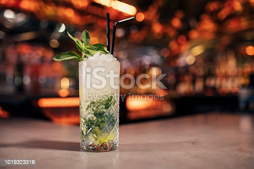 Front view of a mint mojito cocktail on a bar counter. The background of the image is defocused lights and the back of the bar. This is garnished with mint leaves.