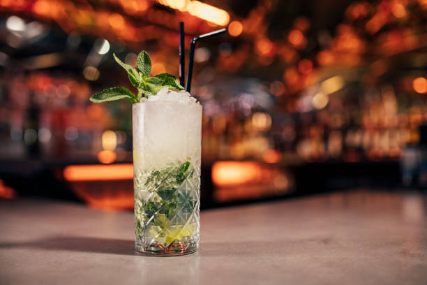 Mint Mojito Cocktail Front view of a mint mojito cocktail on a bar counter. The background of the image is defocused lights and the back of the bar. This is garnished with mint leaves. mojito stock pictures, royalty-free photos & images