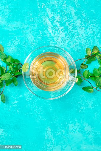 Mint tea cup, overhead shot on a vibrant turquoise background with fresh mint leaves and copyspace