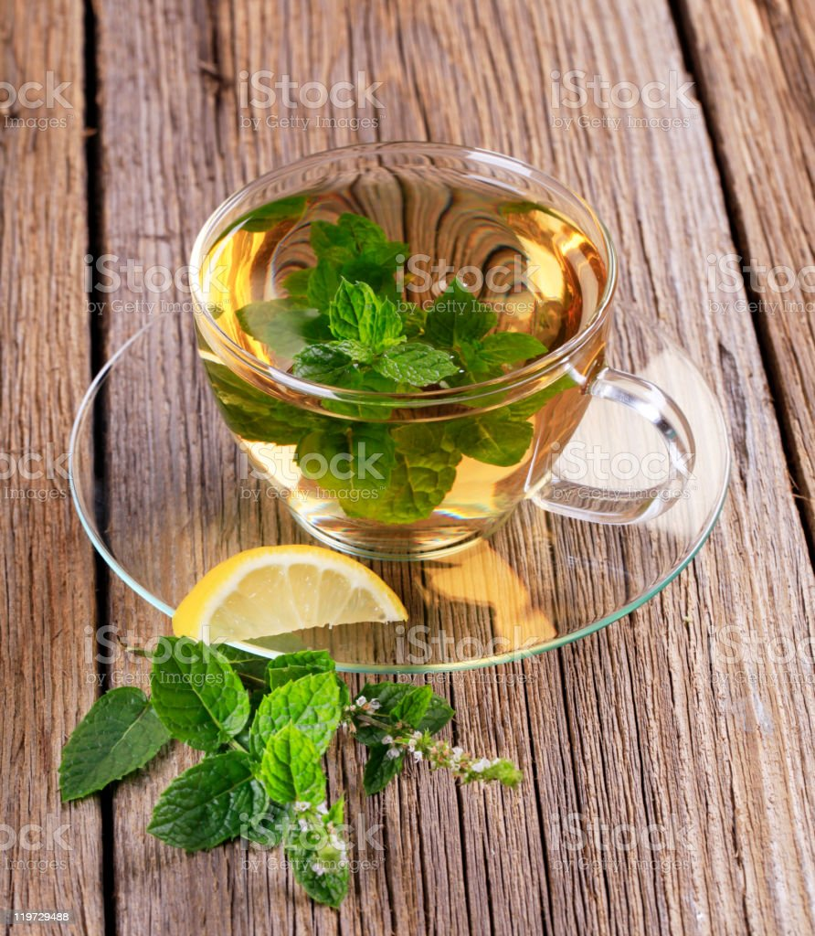 Mint tea in a clear cup with saucer and mint leaves stock photo