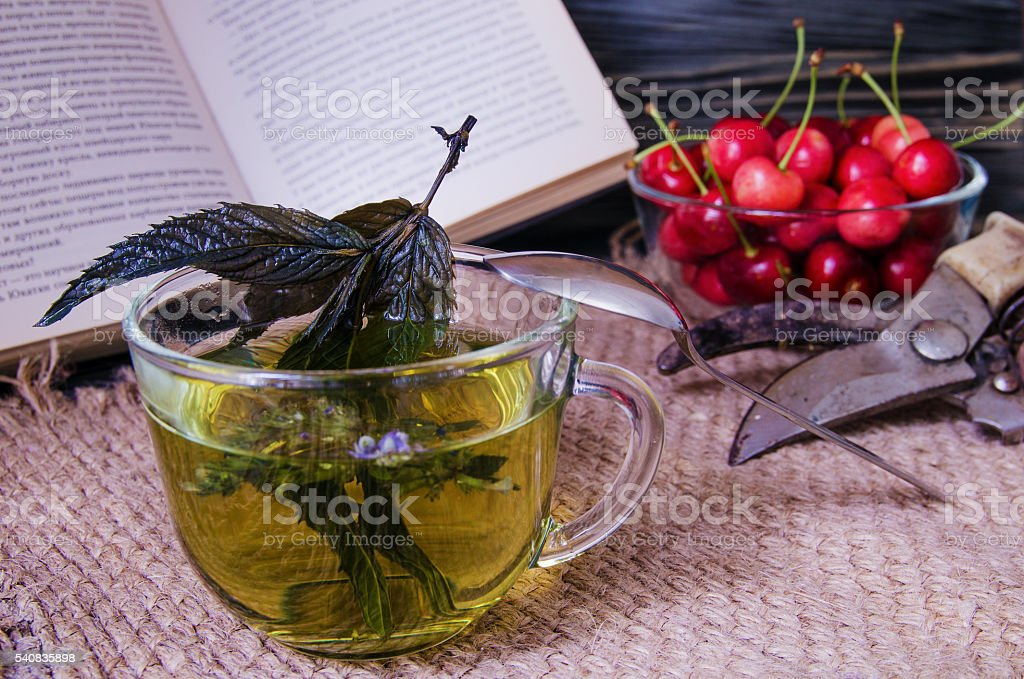 Mint tea in a glass cup with cherries stock photo