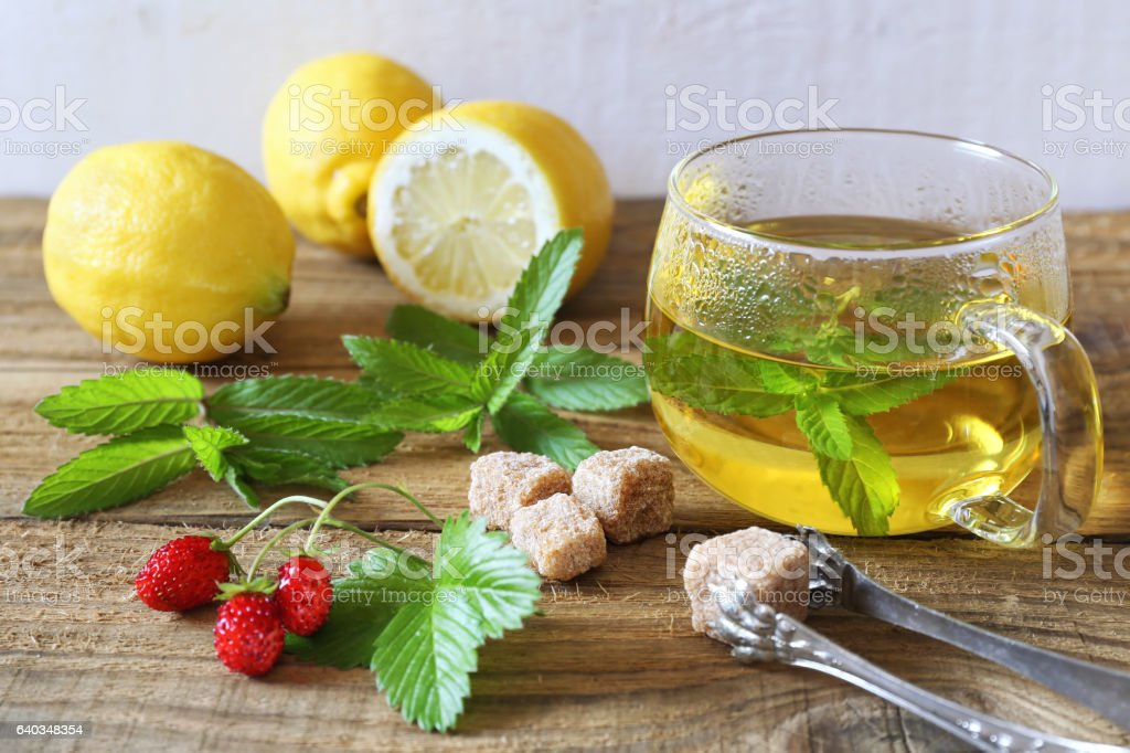 Mint tea in a glass cup with lemons and strawberry stock photo
