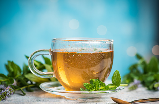 Mint tea in a glass teacup against blue background on a table with copy space
