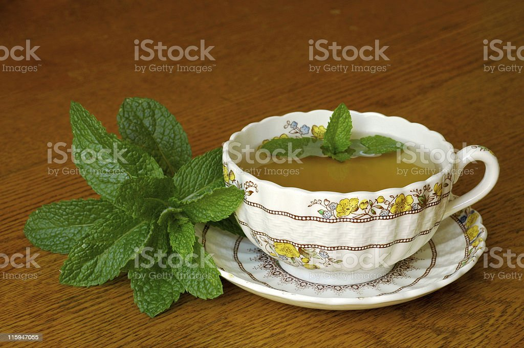 mint tea in floral teacup on wood table royalty-free stock photo