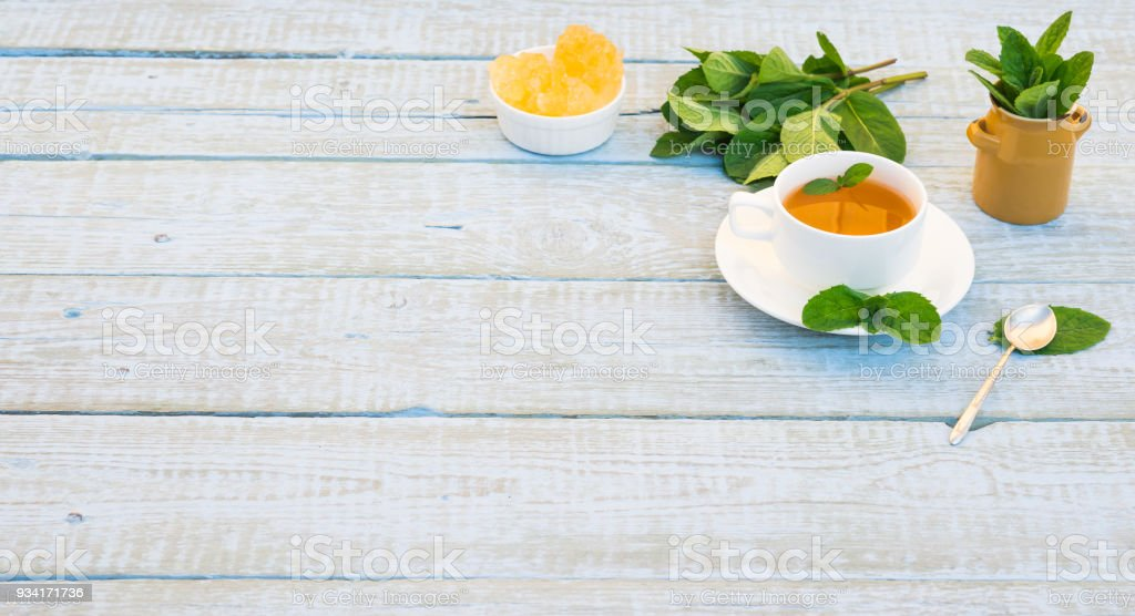 Mint Tea in White Mug. Herbal Tea of Fresh Green Mint Leaves Cup and Crystal Sugar on Rustic wooden Table. Alternative medicine. Traditional herbal therapy. Phytotherapy Medicinal Herbs. Copy space stock photo