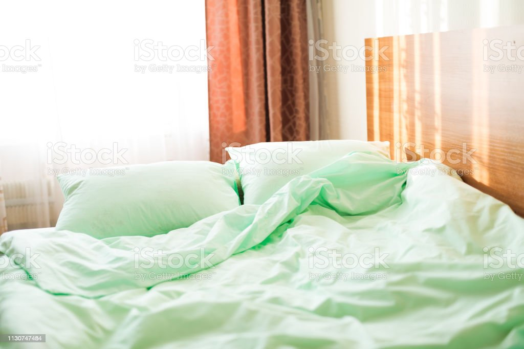 Minty green bedding on the bed at the early sunny morning. Wake-up...