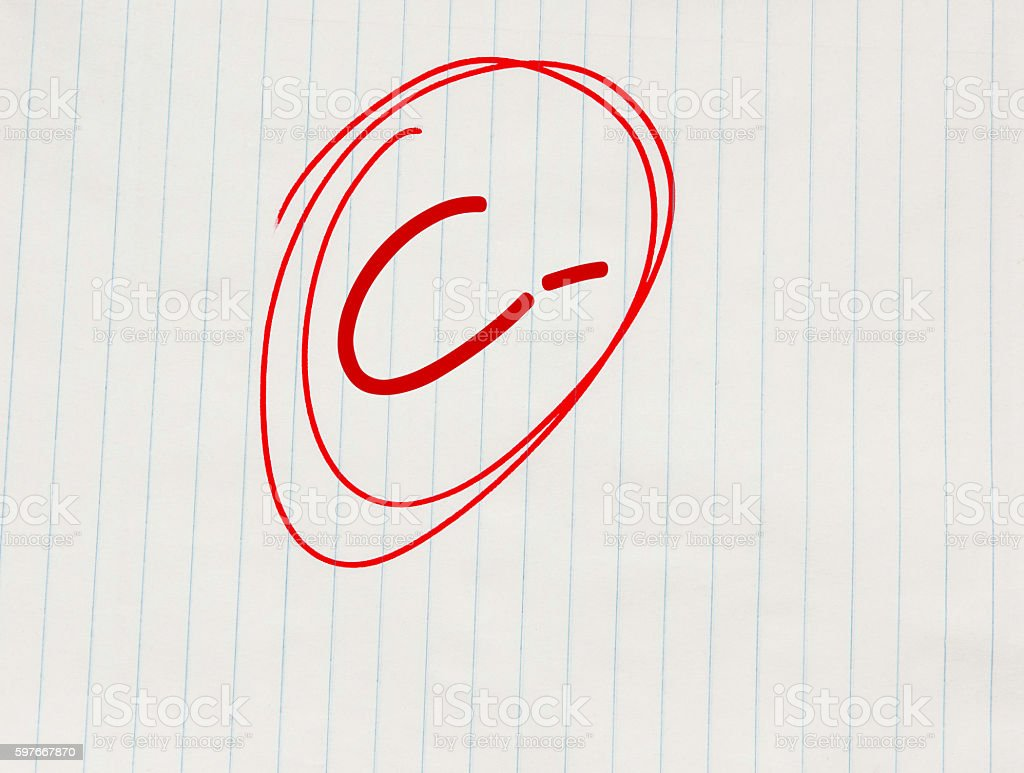 C minus (C-) grade written in red on notebook paper stock photo