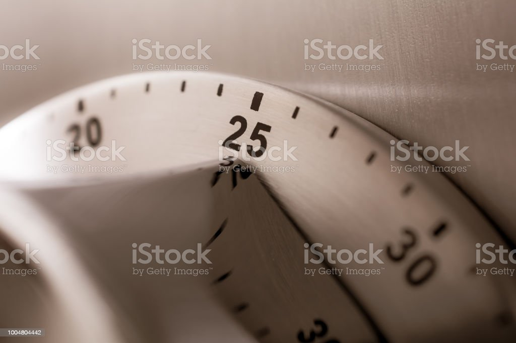 25 Minutes - Analog Chrome Kitchen Timer Placed On A Refrigerator stock photo