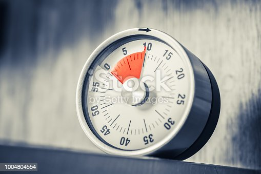 1048940572 istock photo 10 Minutes - Analog Kitchen Timer With Red Mark Placed In A Shelf In Monochrome Colors 1004804554