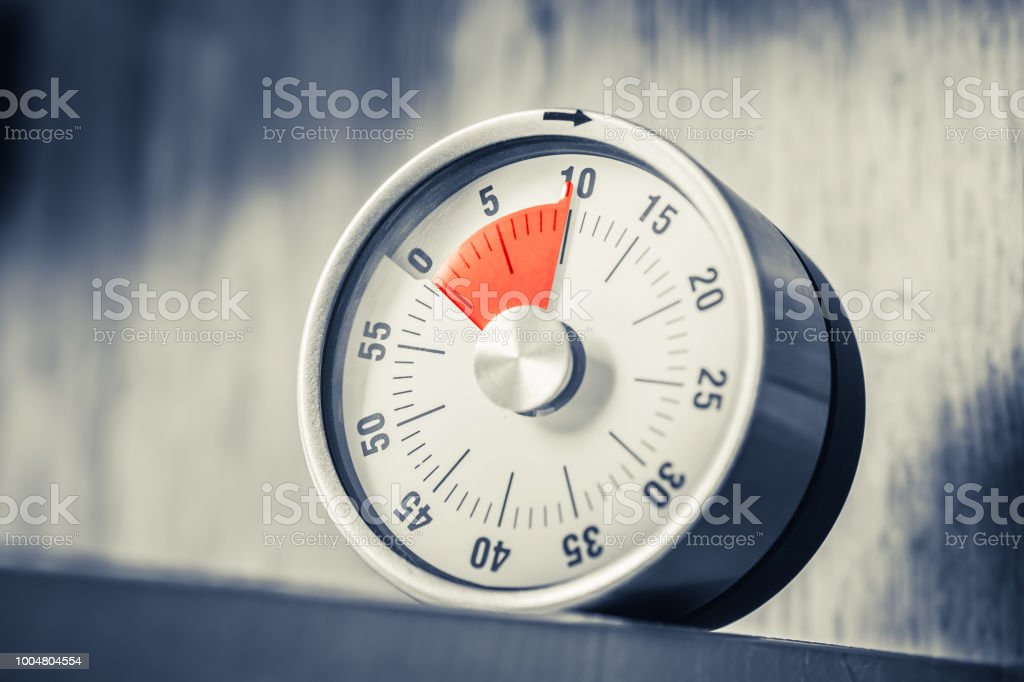 10 Minutes - Analog Kitchen Timer With Red Mark Placed In A Shelf In Monochrome Colors stock photo