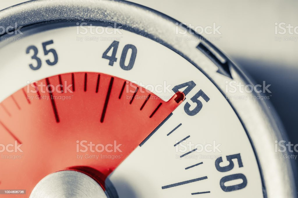 45 Minutes - Analog Kitchen Timer With Red Mark Placed On A Fridge In Monochrome Colors stock photo