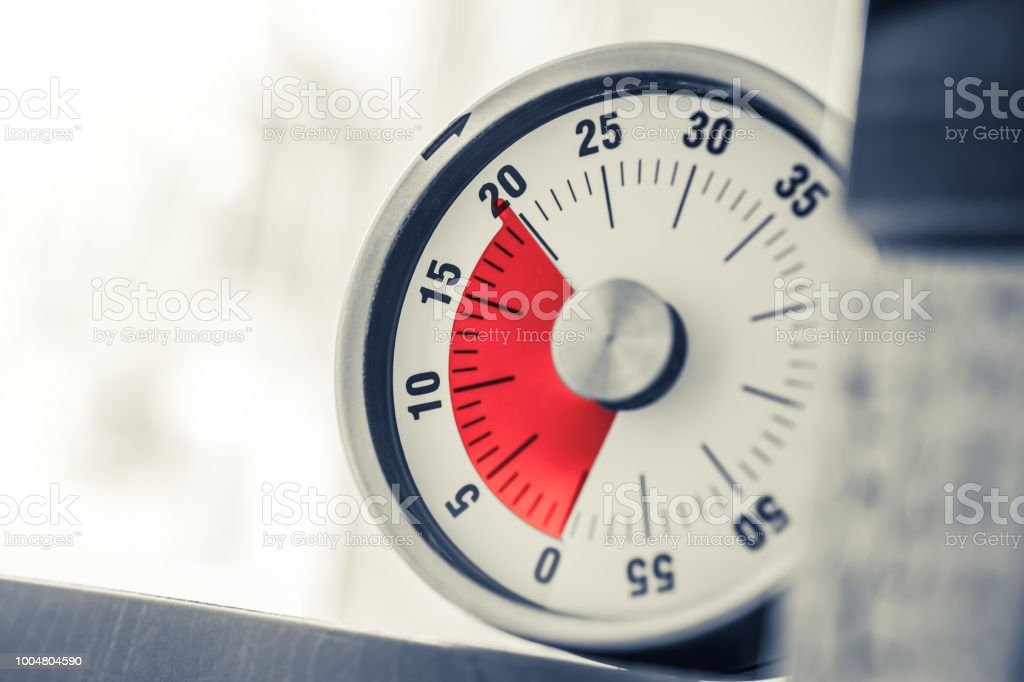 20 Minutes - Analog Kitchen Timer With Red Mark Placed On A Shelf In Monochrome Colors stock photo