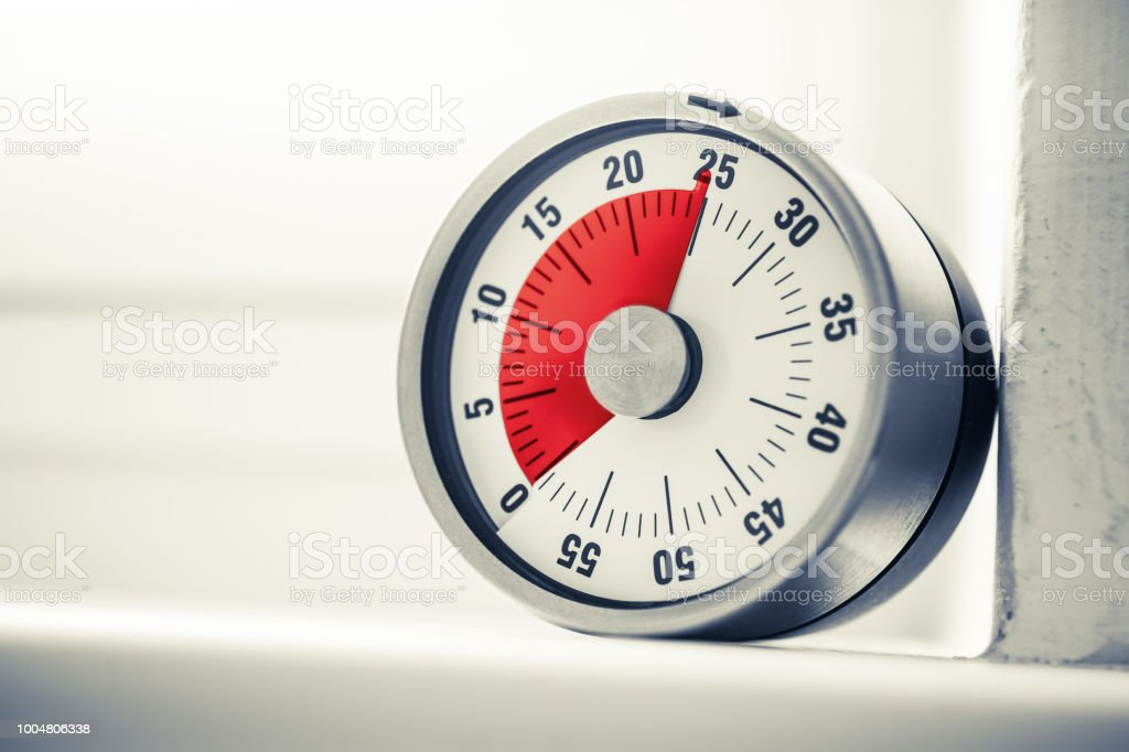 25 Minutes - Analog Kitchen Timer With Red Mark Placed On A Window Sill In Monochrome Colors stock photo