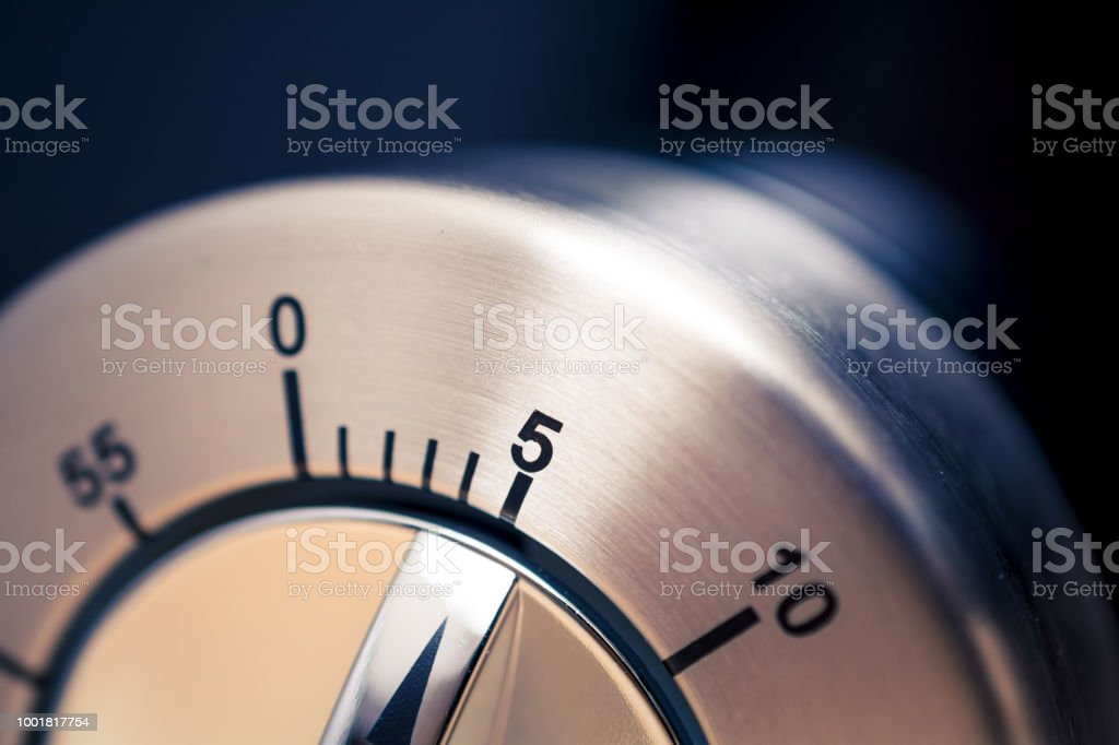 5 Minutes - Close-Up Of An Analog Chrome Kitchen Timer With Dark Background stock photo