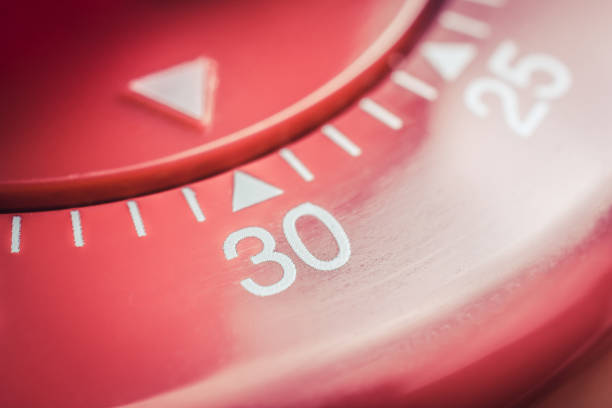 30 minutes - macro of a flat red kitchen egg timer - number 30 stock photos and pictures