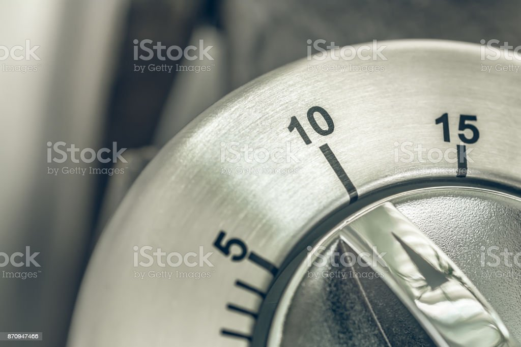 10 Minutes - Macro Of An Analog Chrome Kitchen Timer On Wooden Table stock photo