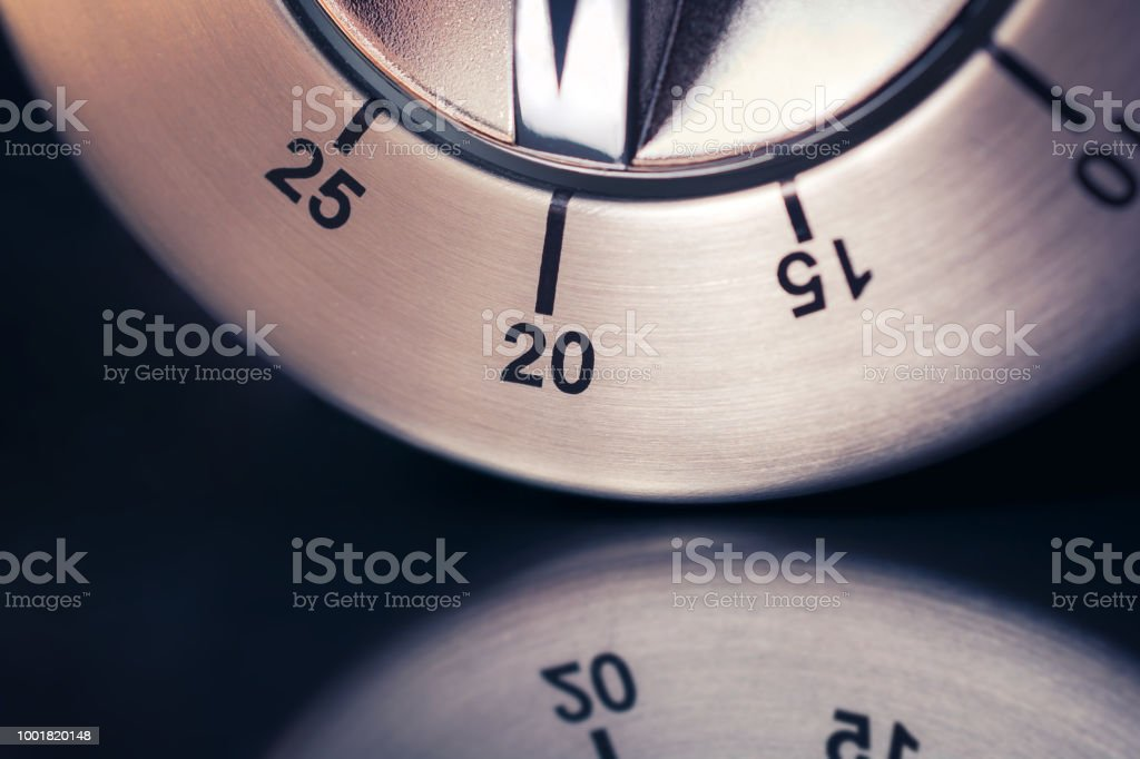 20 Minutes - Macro Of An Analog Chrome Kitchen Timer With Dark Background And Reflection stock photo