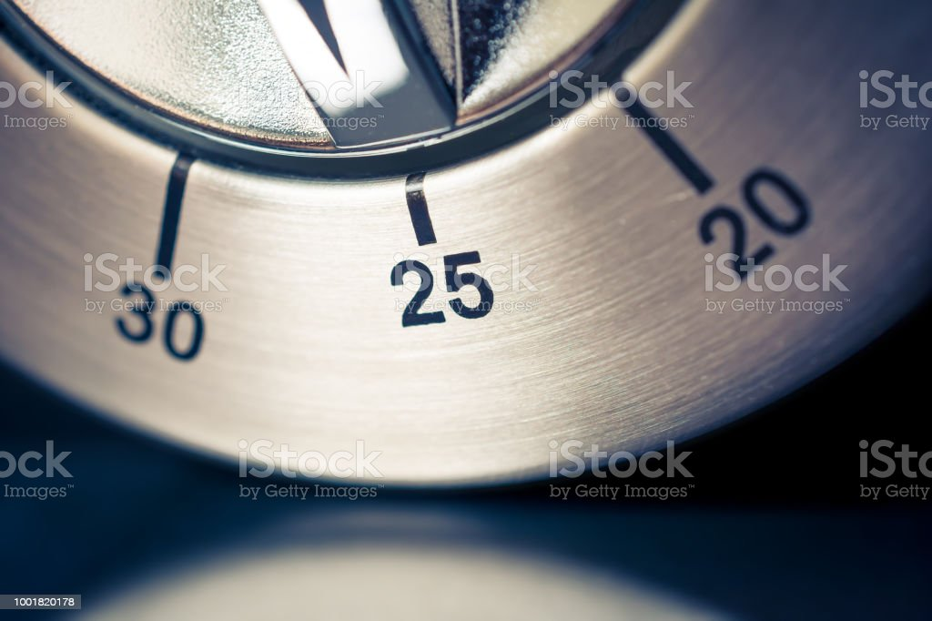 25 Minutes - Macro Of An Analog Chrome Kitchen Timer With Dark Background And Reflection stock photo