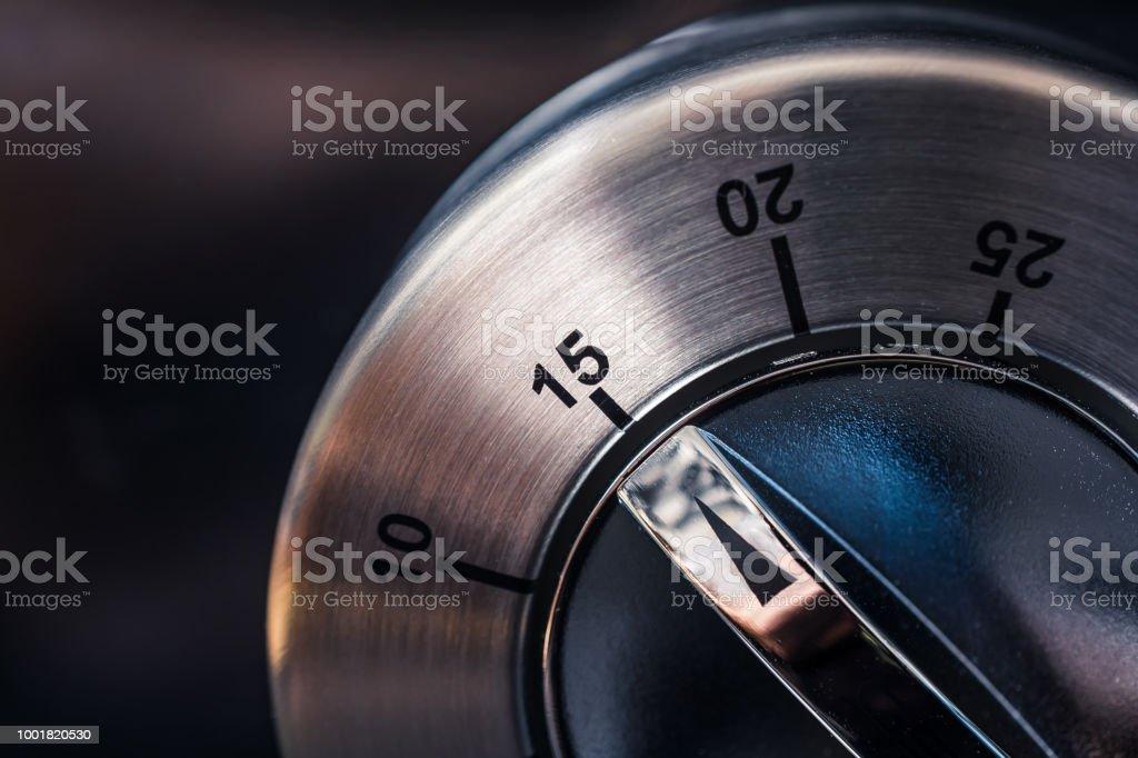 15 Minutes - Macro Of An Analog Chrome Kitchen Timer With Dark Background stock photo