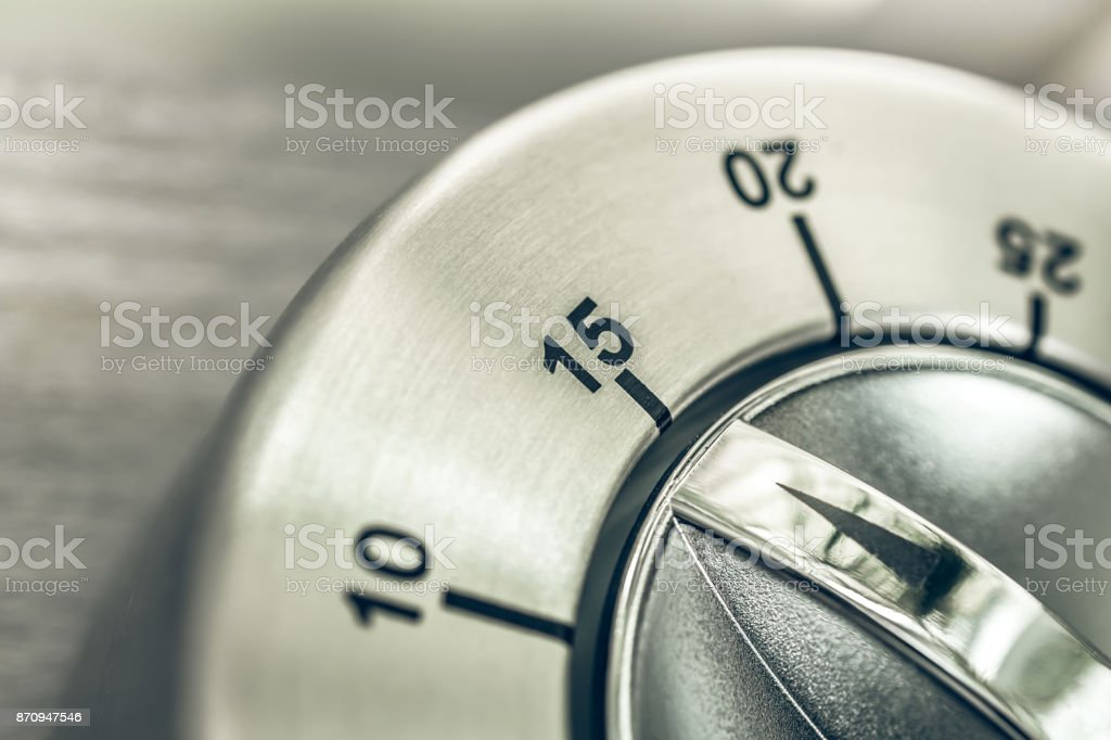 15 Minutes - Quarter Hour - Macro Of An Analog Chrome Kitchen Timer On Wooden Table stock photo