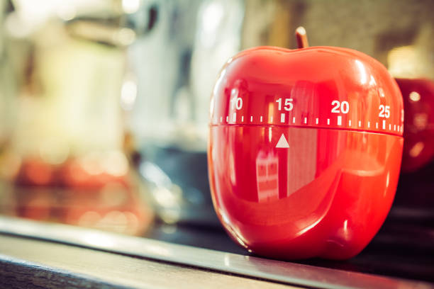 15 Minutes - Red Kitchen Egg Timer On Cooktop Next To A Pot stock photo
