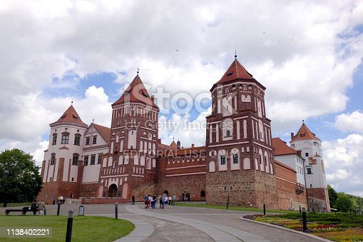 Mir, Belarus - June 13, 2014: Mir Castle on the background of blue sky with clouds summer day, Belarus. Tourists walk around the castle