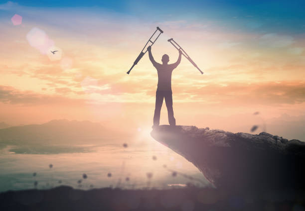 Miracle healing and recovery concept Silhouette a disabled man standing up and raising his crutches at mountain sunset background paraplegic stock pictures, royalty-free photos & images