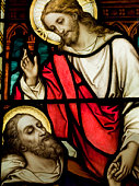 Jesus Christ baptism by Saint John the Baptist on an old stained glass window decoration in Sappada's Church (Belluno) Italy.